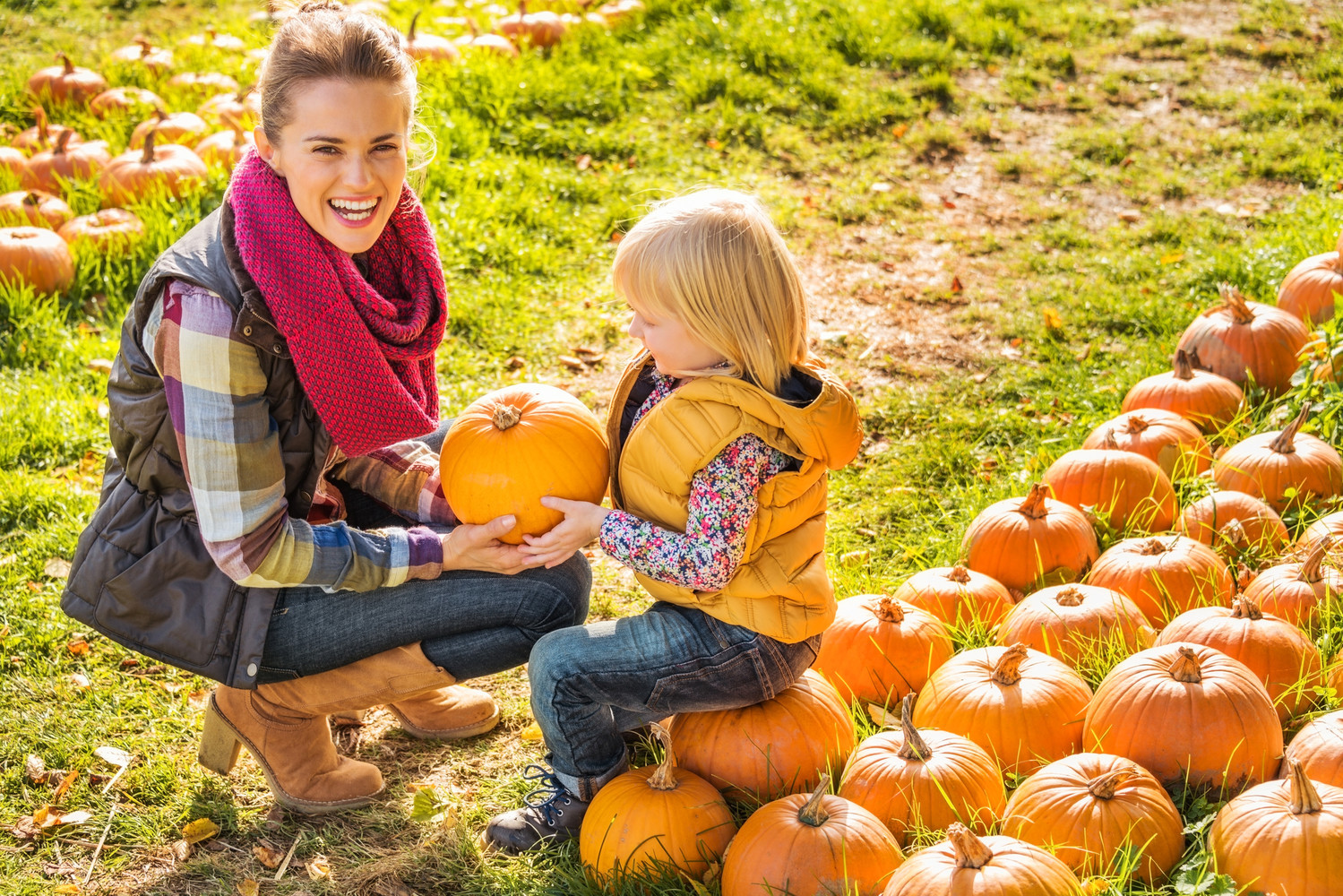 Beautiful smiling woman and child choosing a pumpkin on a pumpkin patch on farm during the autumn season