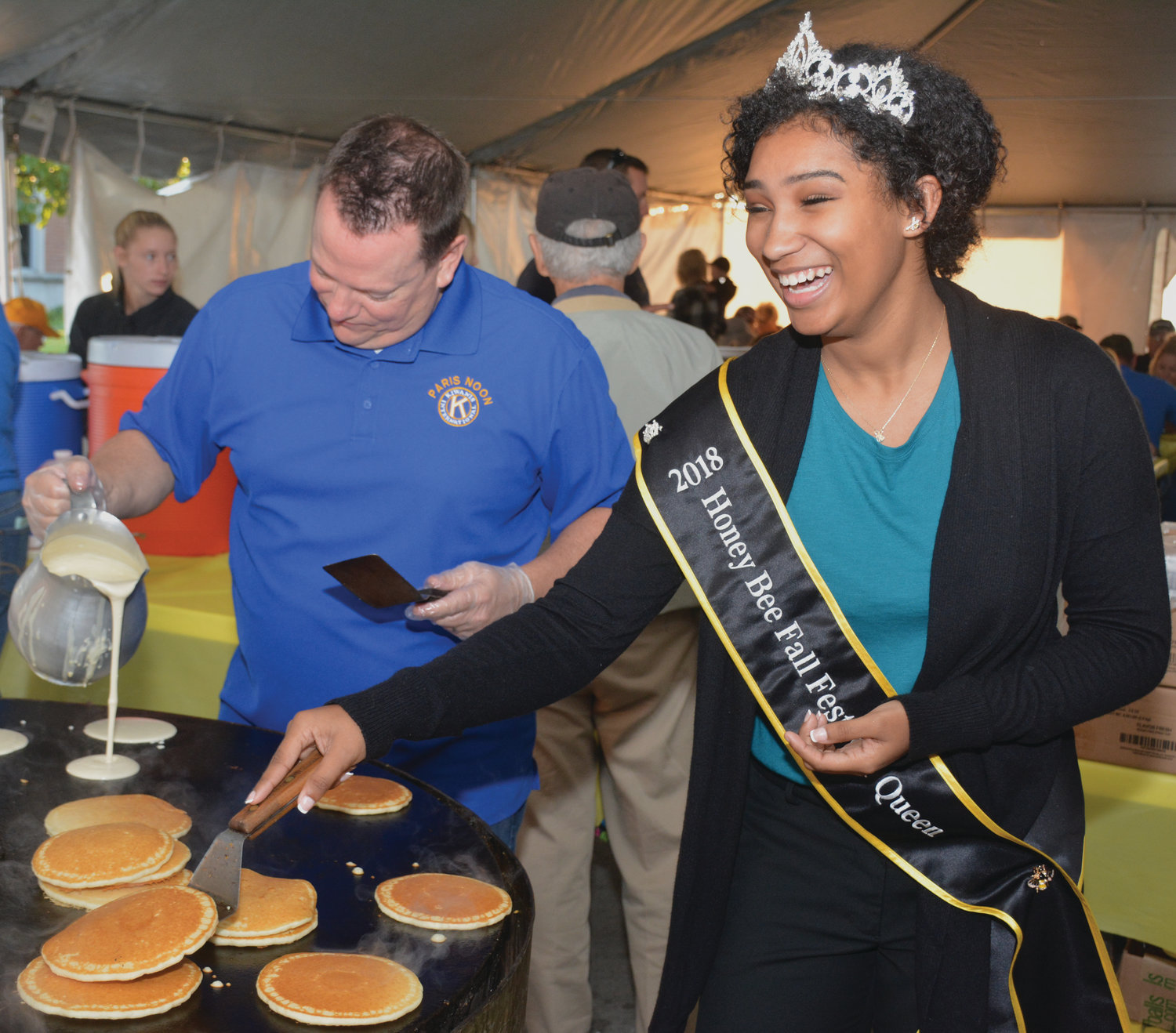 Honeybee Festival Queen Trinity Lee helps Kiwanis Club member Bruce Young cook pancakes Friday morning at the Kiwanis Pancake and Sausage Breakfast. The pancake tent is open again today from 6 a.m. to 1 p.m. on the north side of the square. (Gary Henry/The Prairie Press)