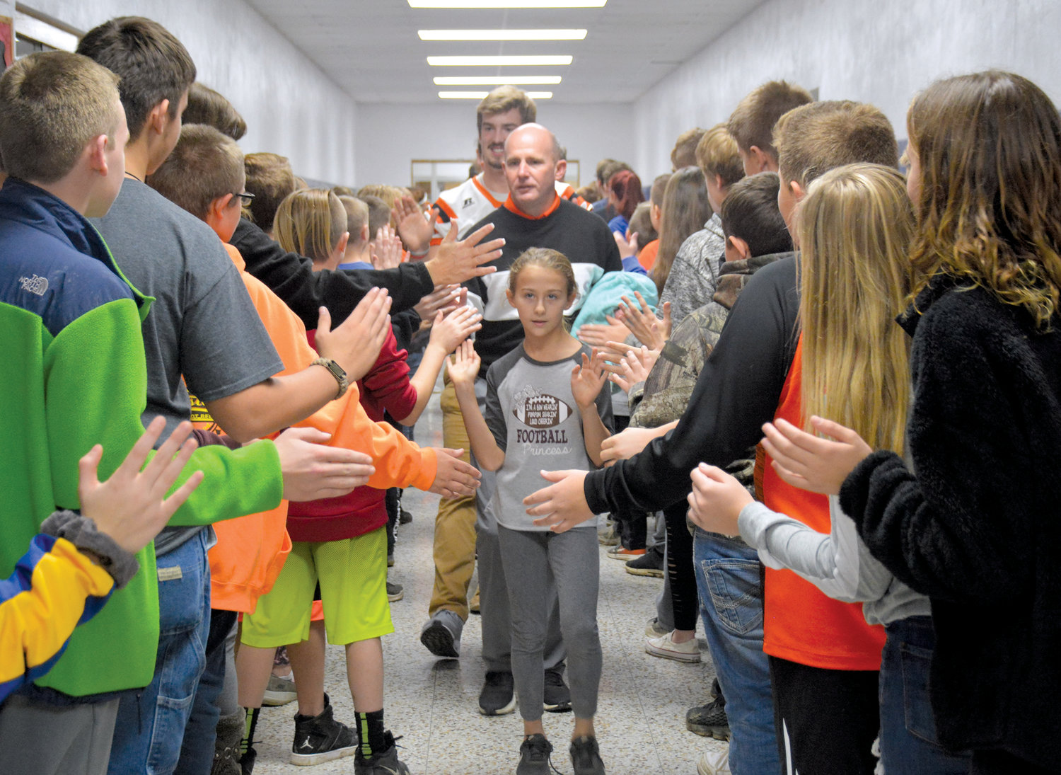 The top Paris Tiger football fan and football princess, Abby Clodfelder, leads her Dad Jeremy Clodfelder and his team through the halls of Crestwood School Friday during the Tiger Team Tour. The team and coaches visited all the Paris schools to the delight of the students who encouraged the team as the travel to Effingham for the second round of the playofffs.