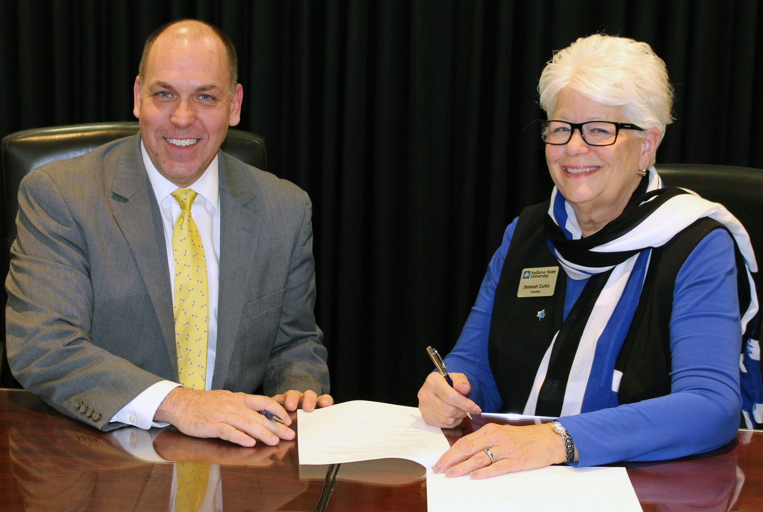 Indiana State University President Deborah Curtis, right, signs the gift agreement making NAL the first formal corporate partner of ISU. At left is NAL president Kirk Gadberry.