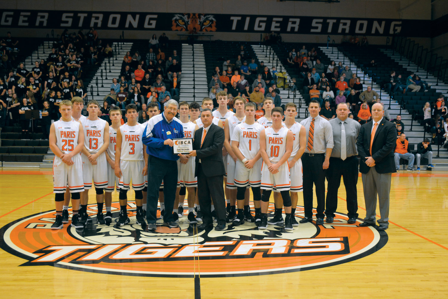 The Paris High School boys basketball program was presented with an award in recognition of having over 1,500 wins in the history of the Paris program.  With 1,768 wins to date, Paris's record ranks in the top 10 of high school programs in the state.  The 2018-2019 Varsity Tigers team, coaches and head coach Shawn Nugent accepted the award from Illinois Basketball Coaches Association representative and Hall of Fame Coach Bruce Firchau.