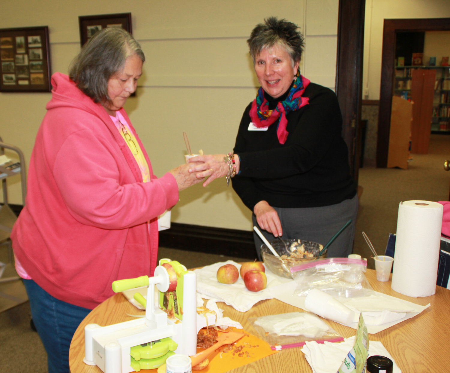 Mary Liz Wright, right, serves a sample of apple salad she made during a demonstration of new kitchen gadgets Tuesday, Jan. 9, at the Paris Public Library.