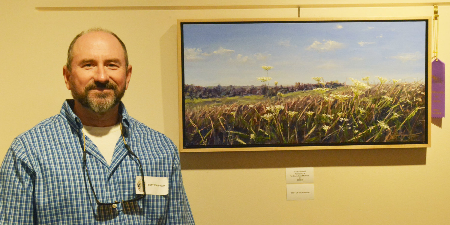 "Curt Stanfield poses with his piece, ""An Endless Moment,"" which won Best of Show at the Painting the Prairie exhibition now at the Link Art Gallery."