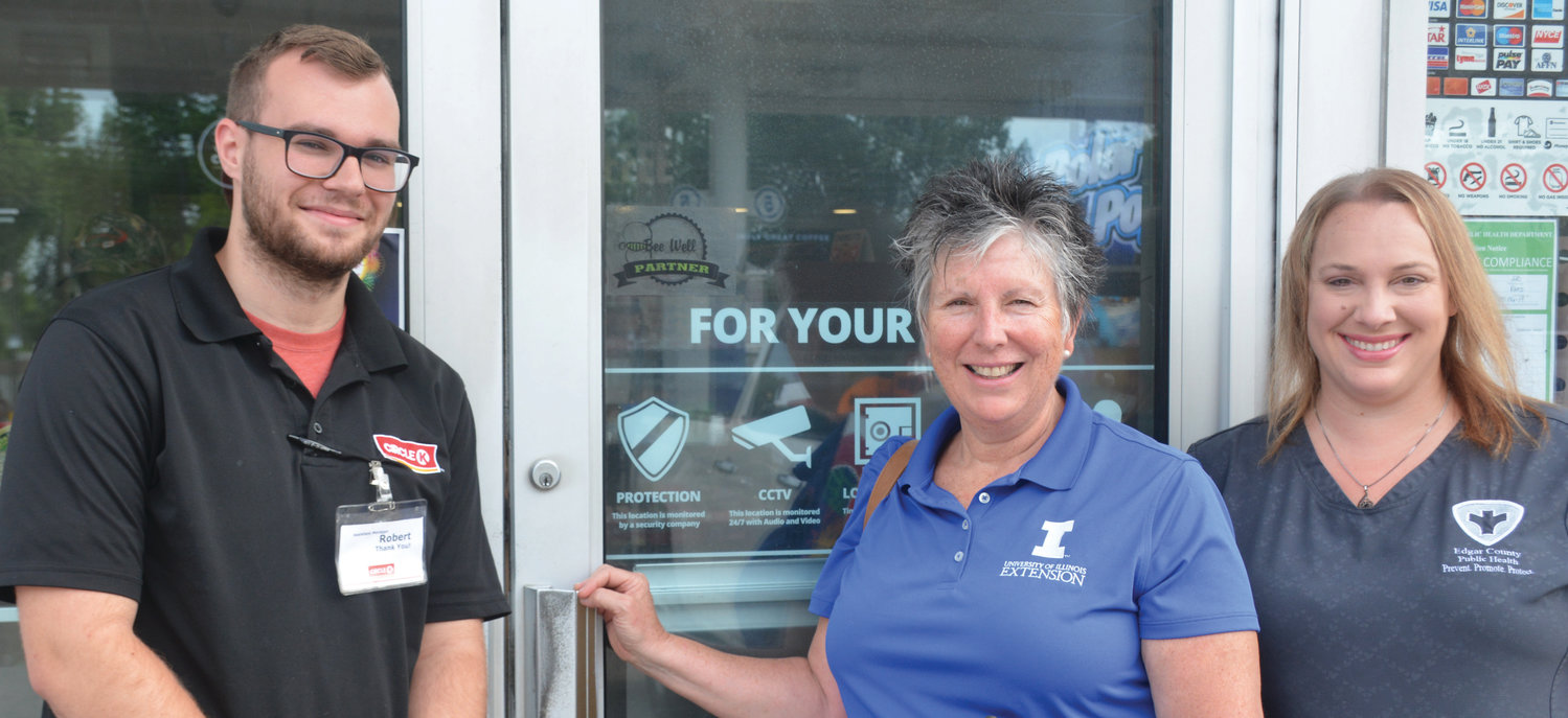Circle K stores in Paris are partnering with Bee Well of Edgar County to raise awareness about making healthy choices when eating and drinking. Robert Sanders, left, the assistant manager of the Jasper Street store has just placed a Bee Well Partner sticker on the door with Bee Well coalition members Mary Liz Wright, center, and Brandi Eaton, right, present.