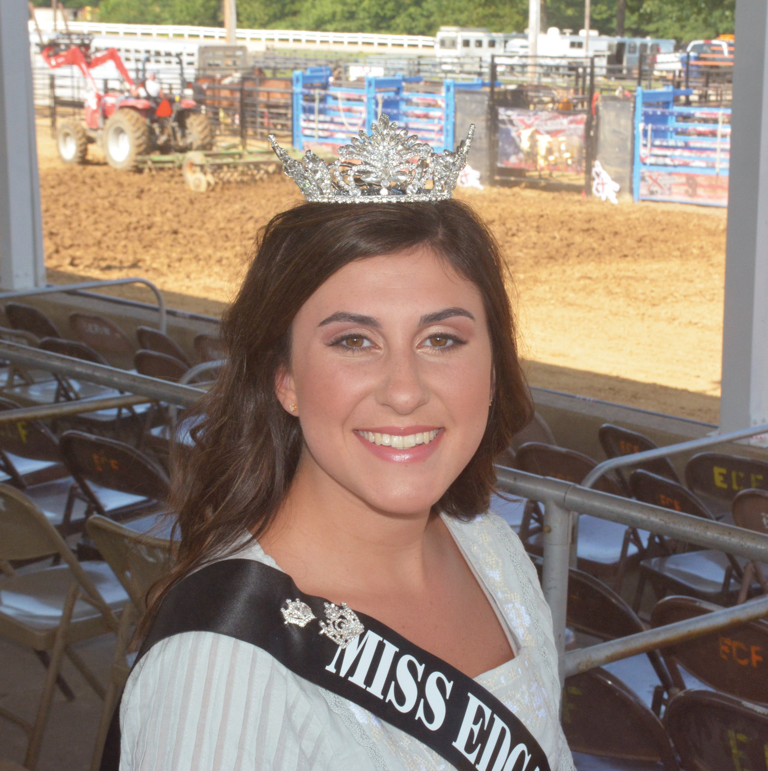 Teresa Twigg, the new Miss Edgar County Fair, sits in the grandstands as work goes on behind her getting the space ready for that night's rodeo performance.