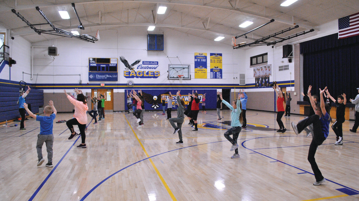 Fourth graders kick up their heels with Ali Antkiewicz during the Healthy Bodies session at Crestwood Elementary. Students measured their mood before and after exercising, and many found they felt happier after their musical workout.
