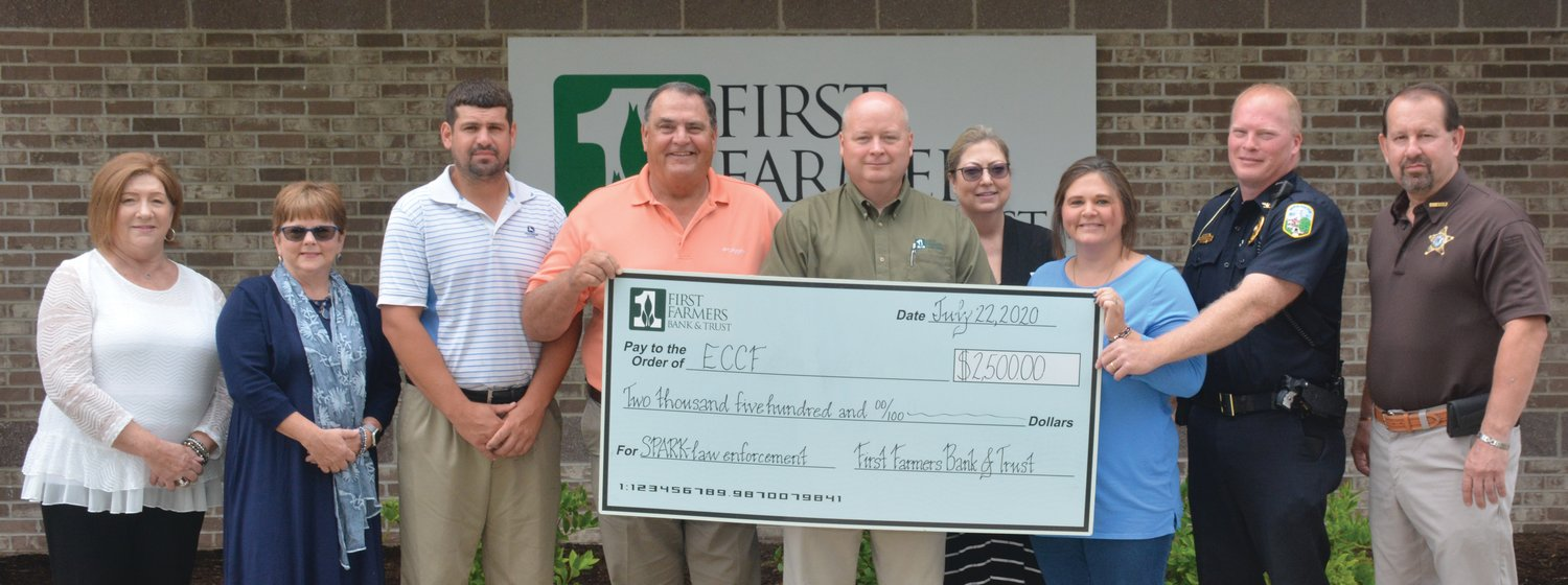 First Farmers Bank donates $2,500 for the effort to purchase heavy-duty body armor and other safety equipment for law enforcement agencies in Edgar County. Left to right, Lydia Laughlin, Sabrina Funkhouser, Jared Trogdon, Larry Daily, Ben Jenness Jr., Sheri Hackett, Tessa Hutson, Paris Police Chief Eric Brown and Edgar County Sheriff Jeff Wood.