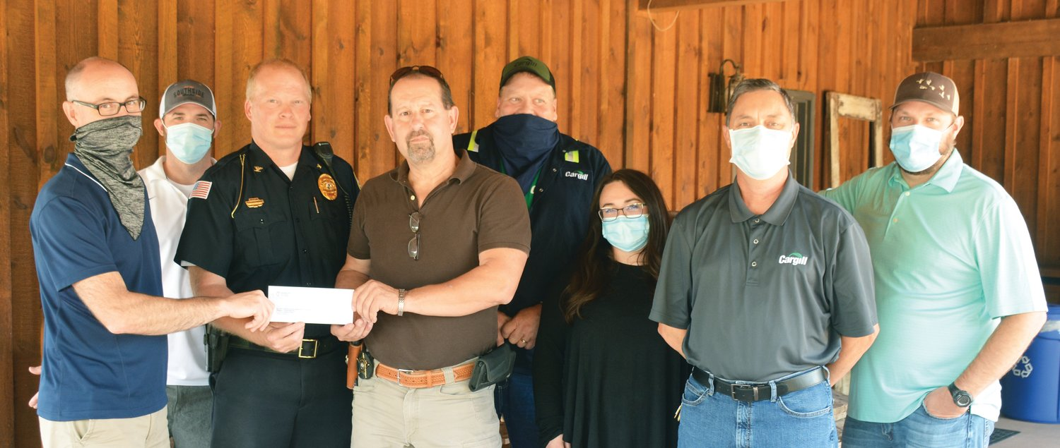 nates $5,000 to the project seeking to buy improved body armor and helmets for every law enforcement officer in Edgar County. Left to right: Mike Carlson, Jeremy Royer, Paris Police Chief Eric Brown, Edgar County Sheriff Jeff Wood, Vince Porter, Kelly Fleming, Mike Laird and Cory Somers.