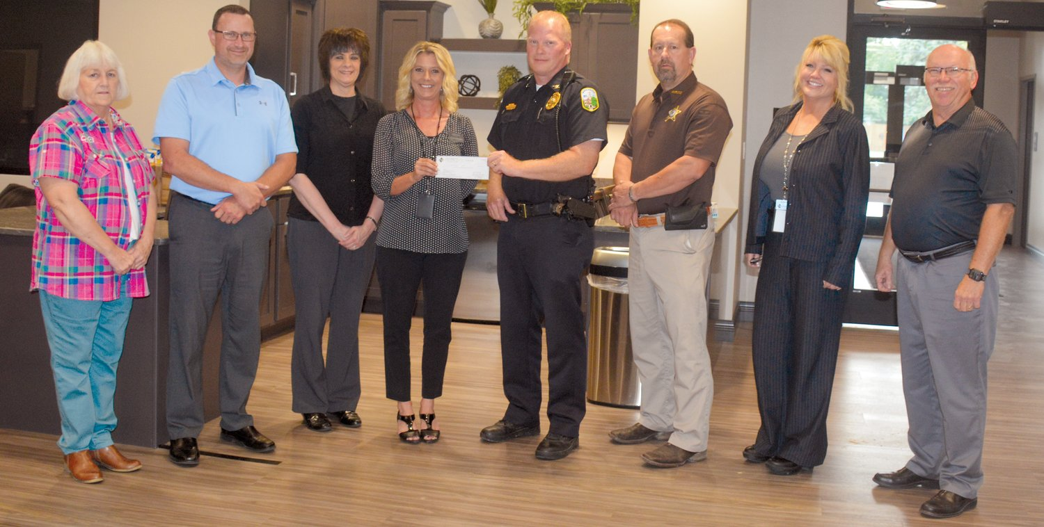 The staff of First Neighbor Bank in Paris presented a check to Friends of Edgar County Law Enforcement in support of the fundraising effort to provide better equipment. Pictured, from left, are Bobbie Throneburg, John Brinkerhoff, Debbie Hefner, Angela Downs, Paris Police Chief Eric Brown, Edgar County Sheriff Jeff Wood, Rachel Patrick and Harry Hughes.