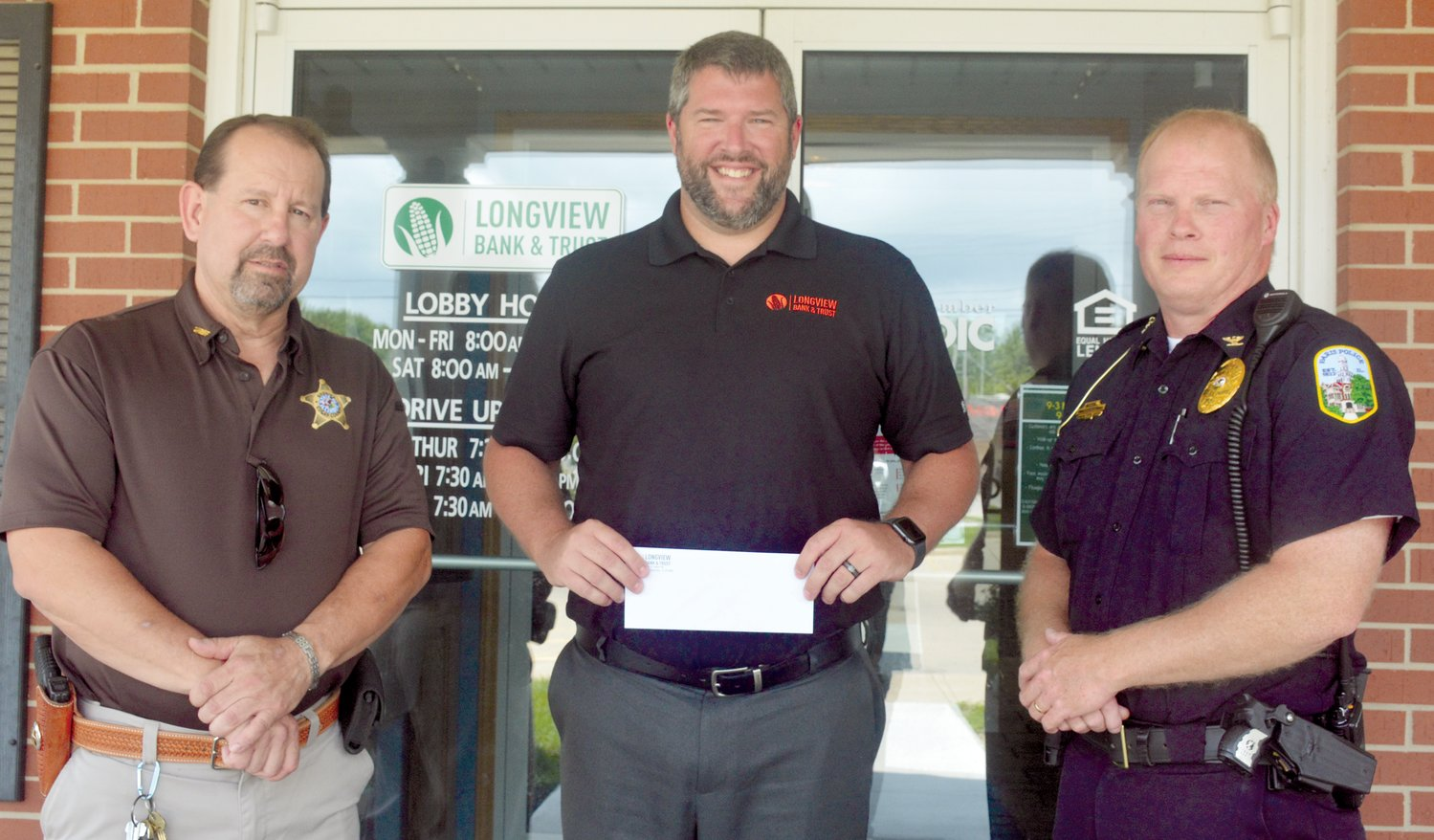Aaron Damler, center, vice-president and branch manager of Longview Bank in Paris, presents a check to Edgar County Sheriff Jeff Wood, left, and Paris Police Chief Eric Brown, right. The check was in support of a fundraising effort by Friends of Edgar County Law Enforcement to provide better equipment to all county officers.