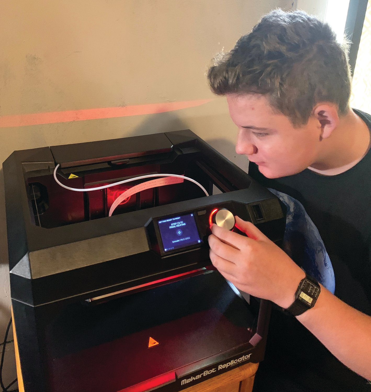 Bryce McGrath works at his 3D printer making special head bands for keeping face masks in place. A Crestwood student, McGrath combined his love of technology and robotics with a  desire to help others in coming up with the idea for the head band.