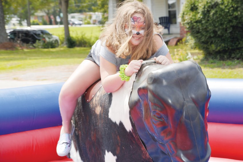 Kiley Brake, 10, gives the mechanical bull a go at the 46th annual Crepe Myrtle Festival in Angier.