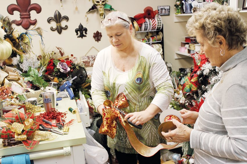 Gleneagles ladies learn how to make Christmas mailbox covers.Sharon Myers, left, shows Martha West how to create a bow with ribbon at Paris in Spring Saturday.