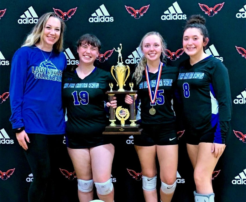 CFCA volleyball players Natalia Brocious, center left, and Anslee McLamb, center right, hold the Falcon Classic championship trophy alongside teammate Reyna Johnson and Lady Eagles coach Brittany Ter Meer in Sanford this past weekend.