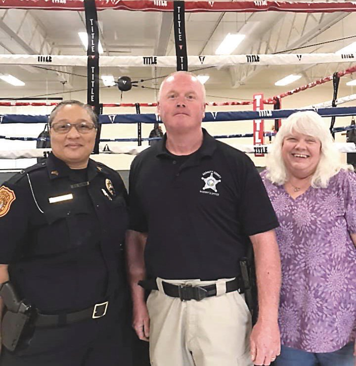 Harnett County Sheriff's Office PAL Director Mark Hornsby, center, stands with Sgt. Gaines, left, and Donna Miller at the program's boxing gym in Lillington. Harnett PAL is set to host 'Back to Boxing' on Oct. 31.