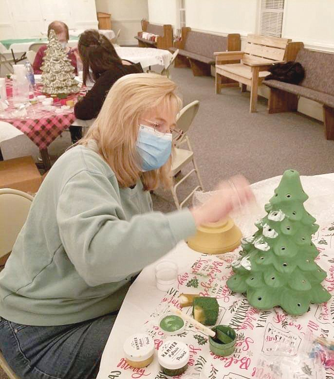 The St. Matthew Pentecostal Free Will Baptist Church Ladies Auxiliary held a night of food, fun and fellowship on Nov. 17. In addition to wearing masks and social distancing, the women painted Christmas trees, decorating them as they desired. Debbie Stewart opened the gathering with scripture and prayer. Here, Deborah Priebe paints a tree. In the background are Sarah Tyndall and Angie Whittington.