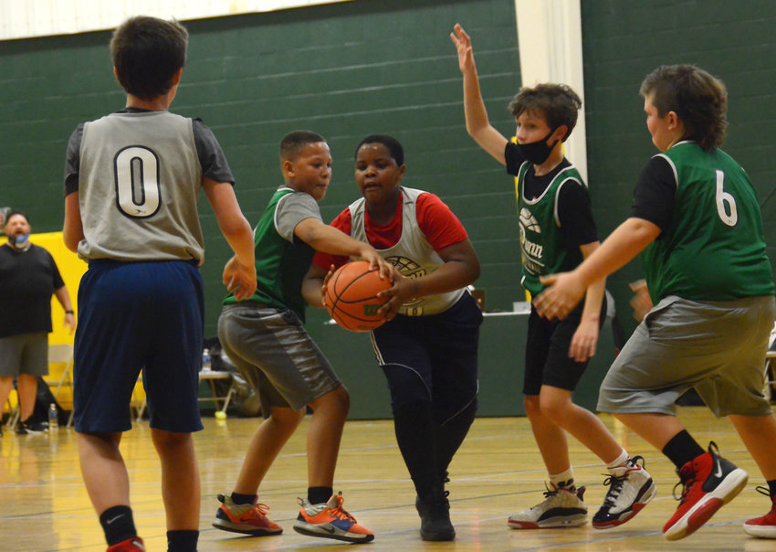 Team 1 player Alexander McKoy Jr., center, is defended by Team 3 players Decari Carpenter, center left, and Kole Daughtry, center right, during a Dunn Parks and Recreation 10-and-under game over the weekend.