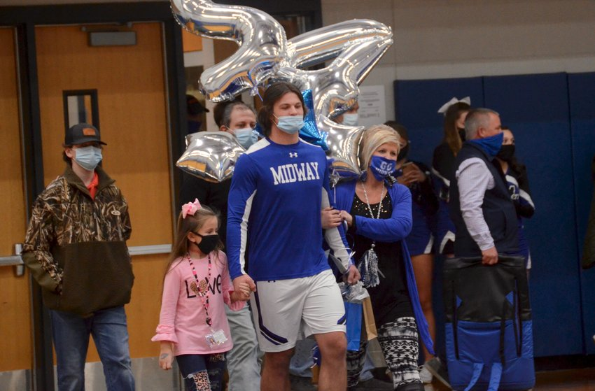 Midway's Tyler Godwin, center, is honored alongside his family during the team's Senior Night celebration at home Friday. Five boys basketball players and two Lady Raiders were celebrated.