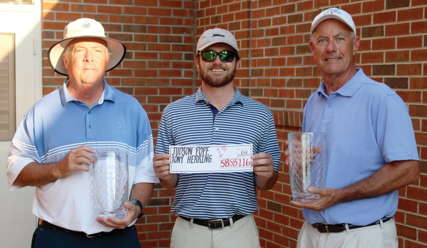 The tandem of Tony Herring, left, and Judson Pope, right, repeated as the Handy Mart Invitational champions Sunday afternoon. The tandem shot a 28-under-par 116, including an. eagle by Pope on No. 18. Pope used a sand wedge. Standing with Herring and Pope is Southern Wayne Country Club Professional Kyle Best.