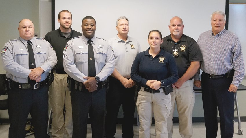 Newly promoted officers in the Harnett County Sheriff's Office are, pictured from left, Coy Poole, promoted to sergeant of patrol; Christopher Marco, assigned to the detective division; Storm Odom, promoted to segreant of patrol; Stuart Stangl, promoted to sergeant of detention; Tracie Champlin, assigned to the detective division; Kevin Ennis, transfered to patrol corporal; and Sheriff Wayne Coats.