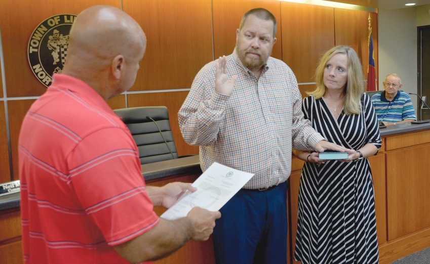 Lillington Mayor Glenn McFadden, left, swears in newly appointed Commissioner Danny Babb as his wife, Lorie, holds the Bible at Wednesday morning's meeting. Babb filled the vacancy left open after the death of Tim Stephens earlier this year.