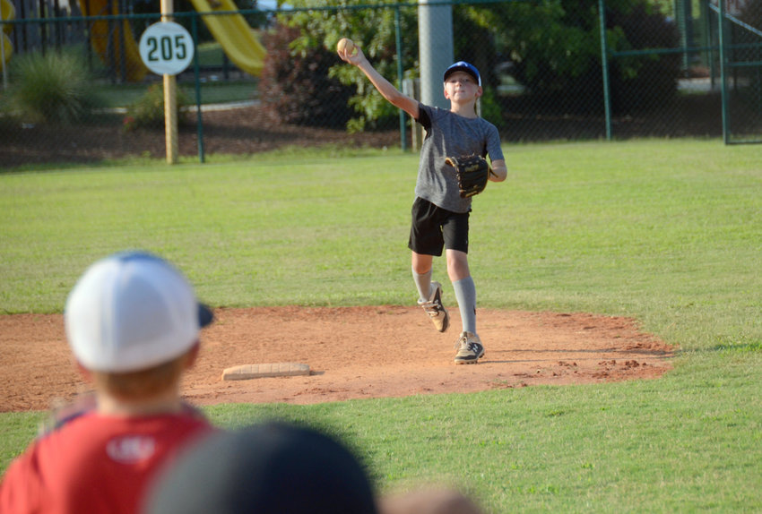 Henry Lawson, center, throws the ball to a teammate during practice at Tyler Park on Tuesday. Lawson and the rest of the Dunn AA All-Stars will compete in the Around the Horn event Friday to kick off this year's Dixie Youth Baseball state tourney.
