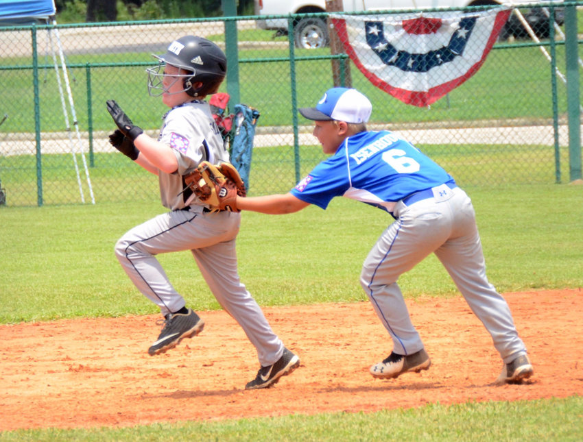 Dunn AA All-Stars' Kole Isenhour, right, tags a South Columbus runner during the teams' first-round matchup of the Dixie Youth Baseball Division 2 state tournament at Tyler Park on Saturday. Dunn went 1-1 on the day.