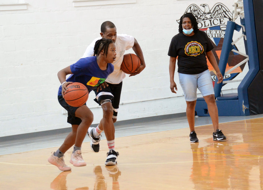 Former Harlem Globtrotter Kashen Cooke, center, and Dunn PAL worker Tara Young, right, work with Triton's Quashaun Williams during a practice drill in Dunn last week. Cooke and Young have partnered to provide a free basketball training service for local athletes.