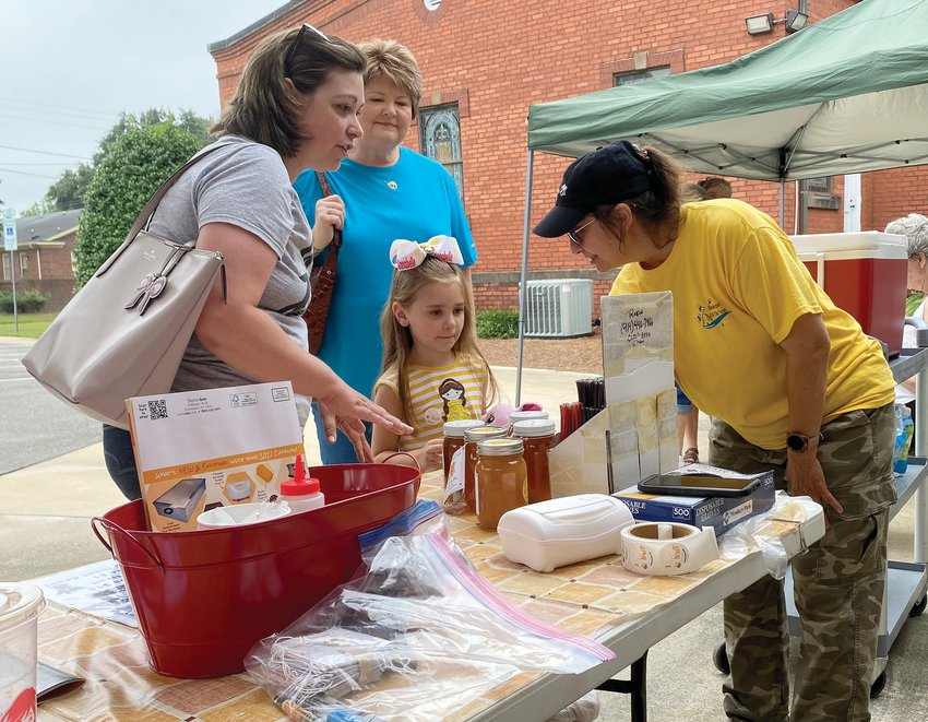 Mount Olive Presbyterian Church held a second farmers' market on Saturday. From left, Jessica Long, daughter Annabelle and friend Eleanor Jones listen to bee keeper Robin DeMark describe the different flavored honey sticks she made from organic honey grown at her bee farm.