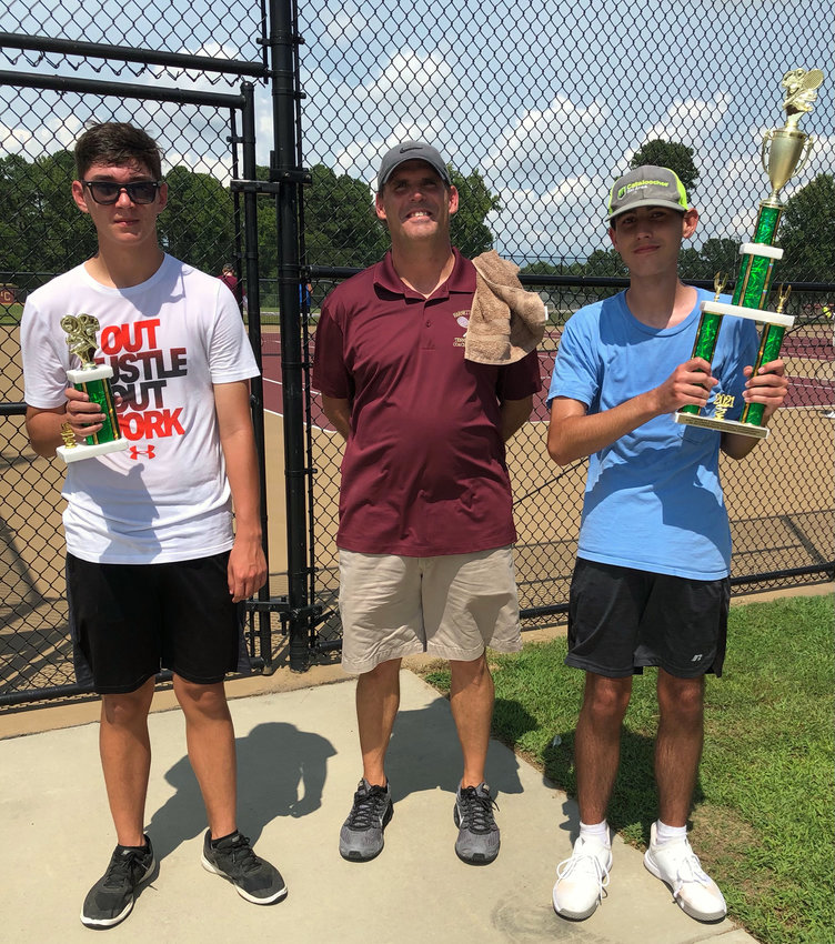 Harnett Central High School tennis coach Jay James, center, stands with Trojans players Reagan Gray and Jacob Brown during Saturday's Harnett County Tennis Academy tournament in Angier.