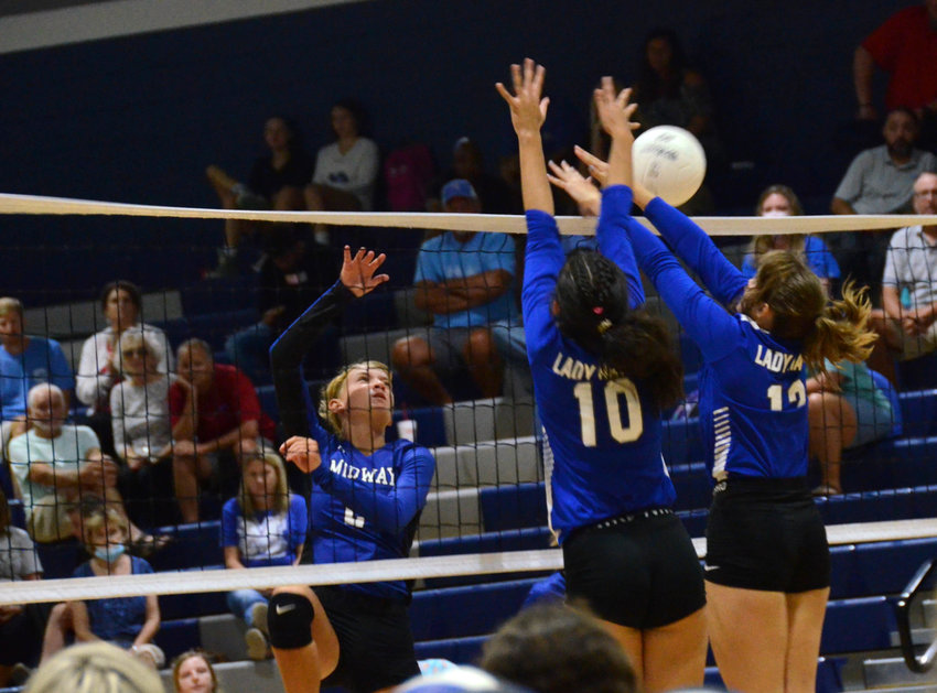 Midway middle hitter Morgan Hall, left, swings a ball past Triton's Carleigh Hemby (10) and Korra Altman during a match in Erwin Wednesday. Hall led the Lady Raiders with 10 kills in the road win.