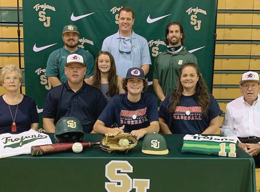 Ayden Wood, center, sits alongside family members while South Johnston athletic director Brody Massengill, back row center, and the Trojans baseball coaching staff look on during a signing ceremony at the school last week. Wood plans to play baseball for Louisburg College. The senior infielder helped South to a 7-7 overall record and a 6-4 conference mark this past season.