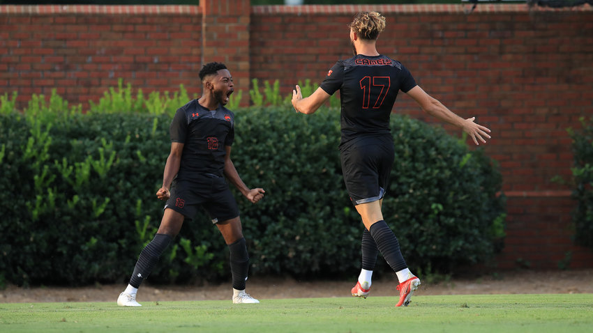 Campbell's Tyler Young, left, celebrates after scoring one of his two goals at UNCG Thursday. The Camels won by a 3-1 decision.