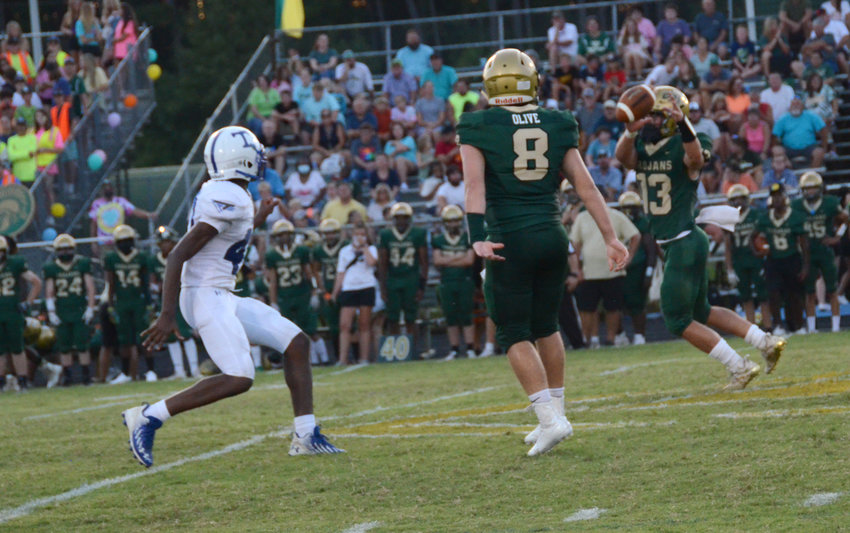 South Johnston's Paul Olive (8) flips a short toss to Brayden Barefoot, right, with Triton defensive end Kenny McKoy in pursuit during Friday's contest in Four Oaks. Olive and Barefoot combined for three touchdowns in the 33-20 win.