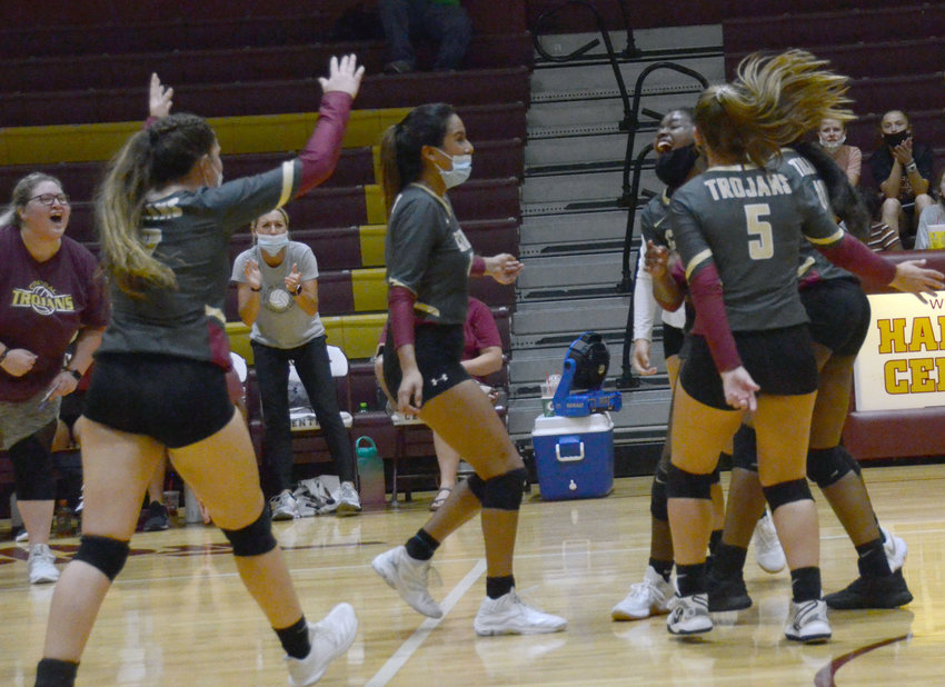 Harnett Central first-year coach Ashley Gaines, far left, joins a group celebration during the team's win over Western Harnett at home Tuesday. The victory marked Gaines' first as head coach.