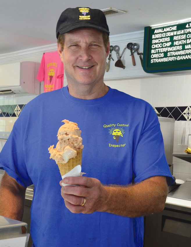 Scott Wilson serves up a cone of ice cream at Sunni Sky's in Angier Thursday.