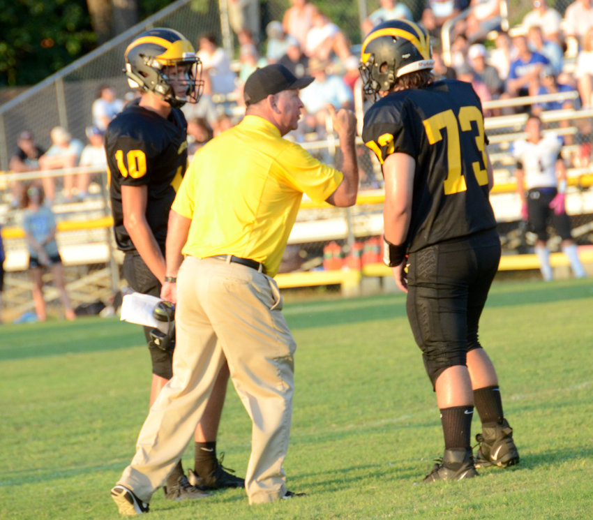 Hobbton coach Joe Salas, center, chats with offensive tackle Austin Bradshaw (73) and quarterback Loden Bradshaw during a home game on Aug. 23. The Wildcats (1-1) offense has collected 163 points through two games this season.