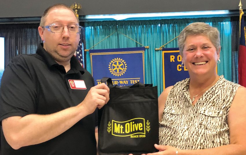 Rotary of Mount Olive President David Martin, left, presents a gift to Mount Olive Area Chamber of Commerce President Julie Beck during an August meeting.
