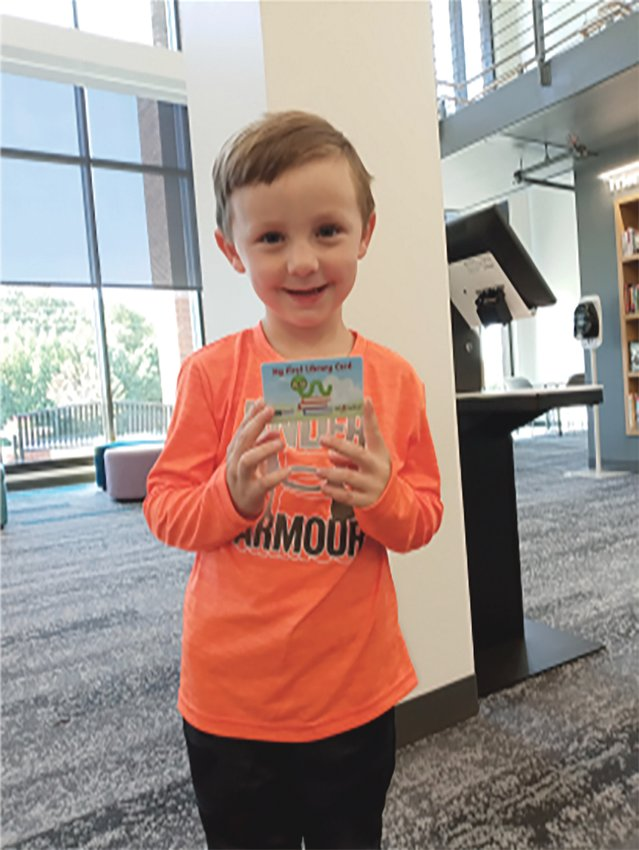 Grayson Wheeler proudly shows off his first library card after signing up at the Harnett County Public Library.