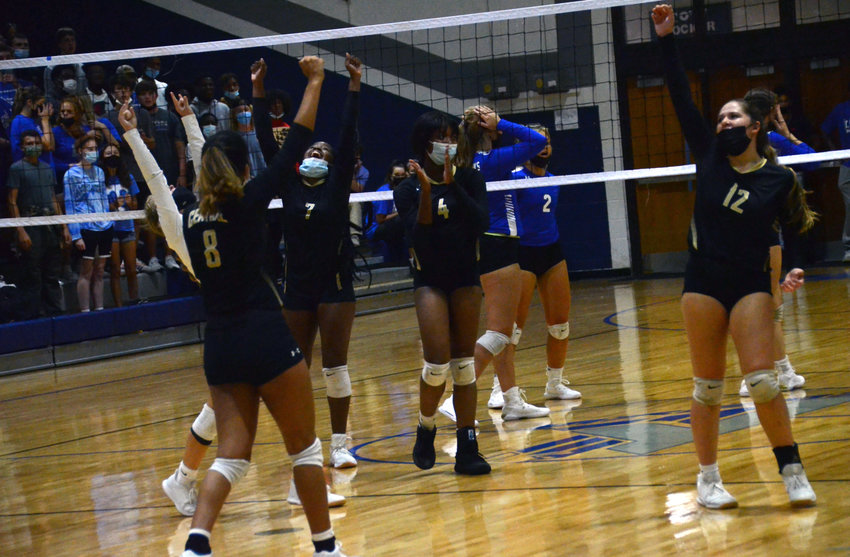 Harnett Central's Ivanna Jones (7), KeErica Snead (4) and Carlee Harrell (12) celebrate a point during Tuesday's road win at Triton.