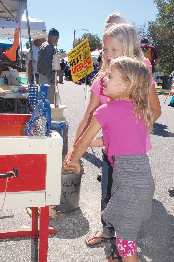 Brooke and Krista Brandon enjoy grinding corn at an exhibit at the Cape fear Fest in 2017. The booth was set up by the Sandhills Antique Farm Equipment Club.