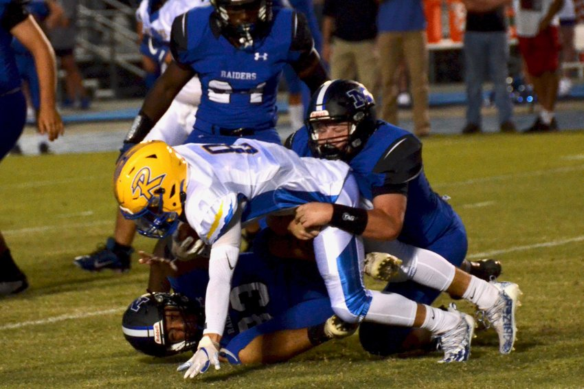 Midway linebackers Cooper Bryan, right, and Aldo Lazcano-Navarette, bottom, combine for a tackle during the first half of Friday's home win over Richlands. The Raiders defense forced three turnovers in the team's third straight victory.