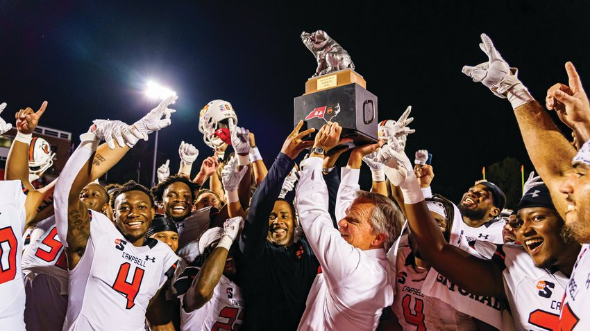 Campbell football coach Mike Minter, center left, holds the N.C. East/West BBQ Bowl trophy after the Camels topped rival Gardner-Webb on the road this past Saturday.