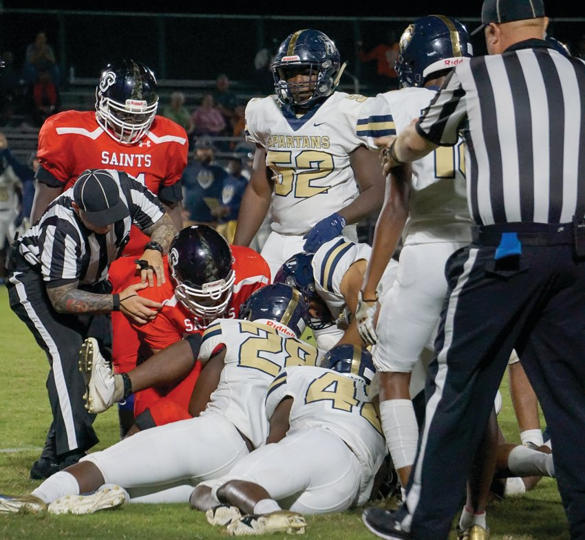 A referee digs into the pile of players to determine who recovered a fumble during Southern Wayne's homecoming game against Smithfield-Selma on Friday evening.