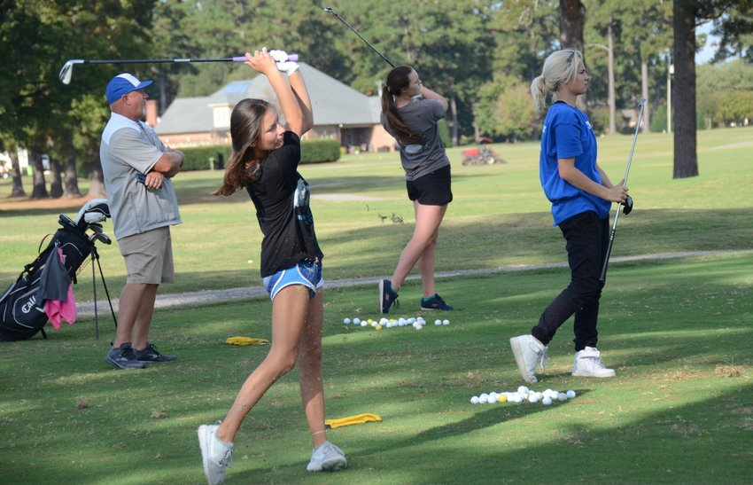 Triton coach Mark Whitman watches golfers, from left, Neva Chance, Sueanna Bass and Tristan Ennis during practice at Chicora Golf Club last week. The trio is set to compete at the 3A East Women's Golf Regional on Tuesday.