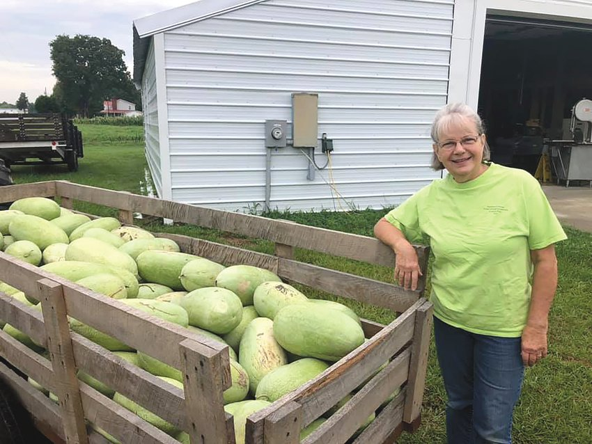 Claudia Farr, who leads the Lillington United Methodist Church Garden Project, stands next to a trailer filled with watermelons. Volunteers grow produce and donate to agencies that help people who are food insecure.