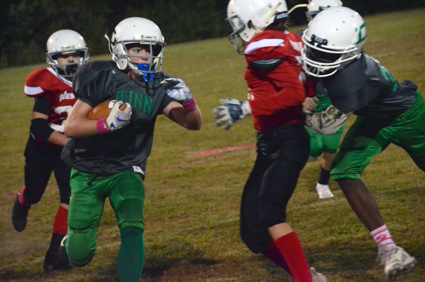 Dunn running back Alan Hinson, left, runs against a Western Harnett Red defender during a 13-and-under contest at Tart Park on Wednesday. Dunn won 14-6 as part of the parks and rec Pink-Out event.