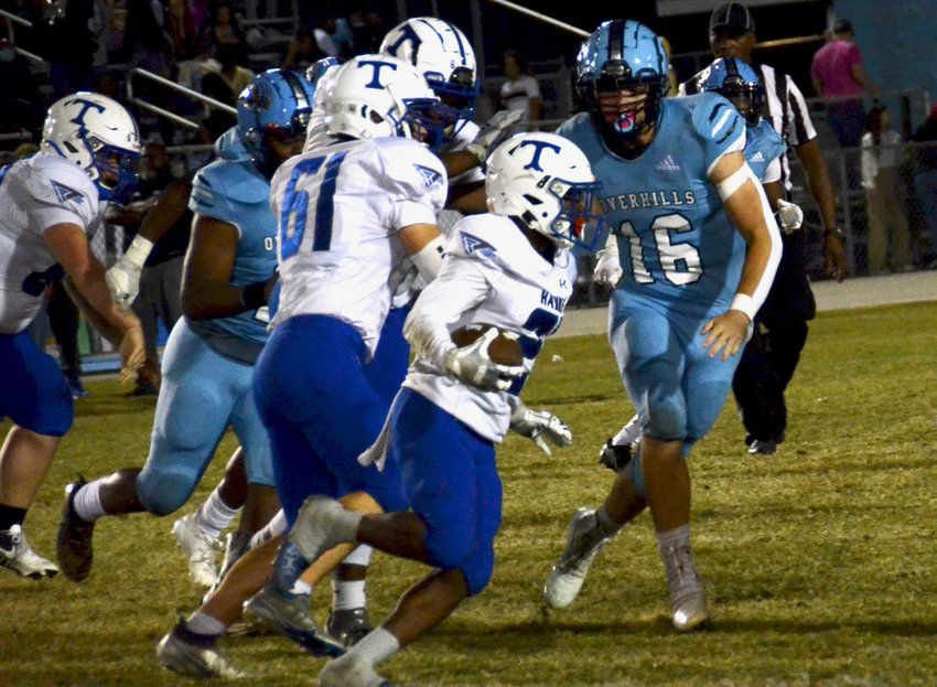 Triton running back Camauri McDougald, center, tries to hit the edge against Overhills defensive end Hunter Berryhill (16) during Friday's game in Spring Lake. McDougald finished with a team-high two rushing touchdowns.