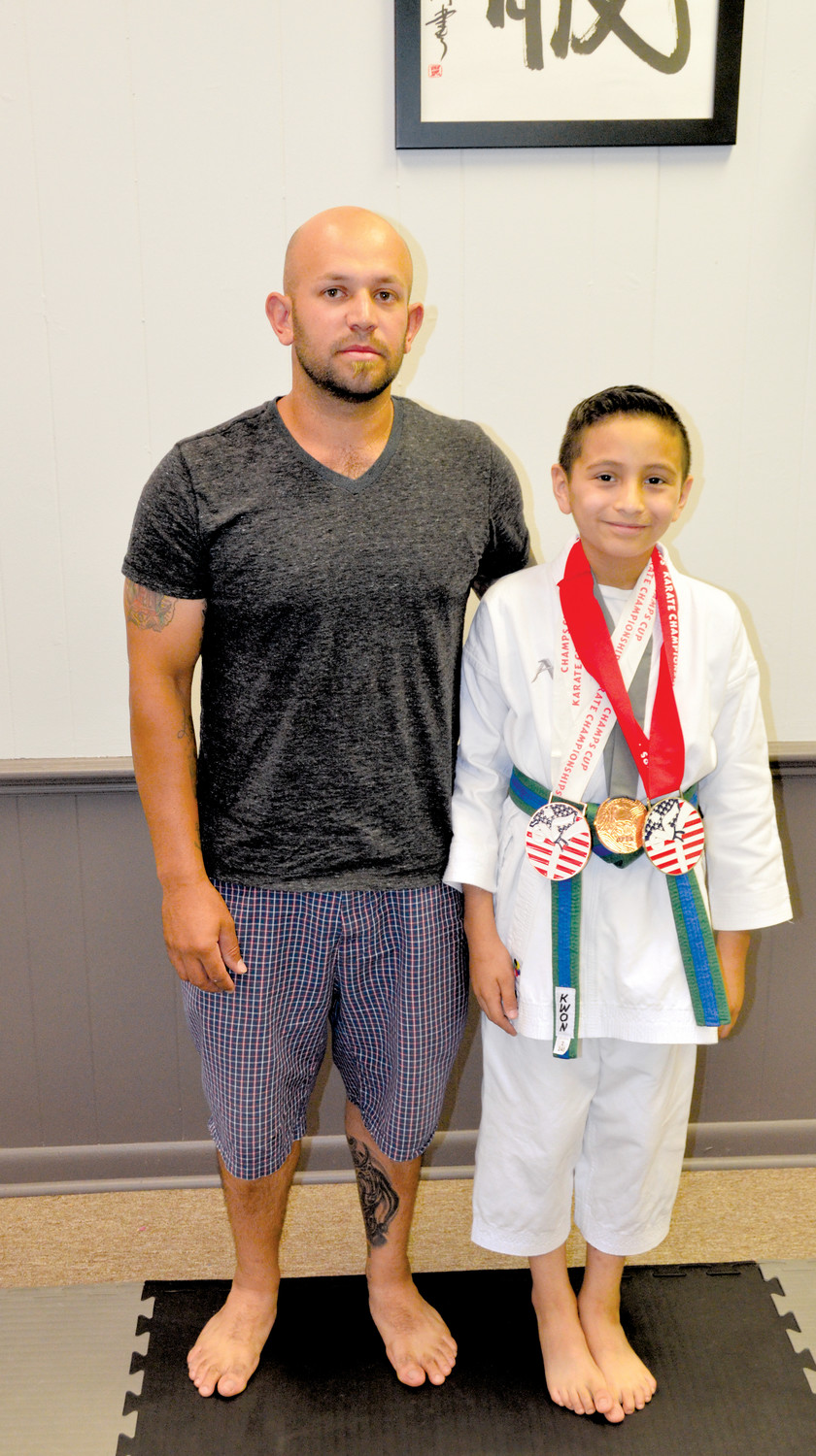 Kaled Garcia, 9, of Clement stands with his father, Julio Barajas. Kaled recently won three medals, a silver and a bronze in Douglasville, Ga., and a bronze for his Kata, in Greenville, S.C. 'I was impressed that I tried my best and got medals.'
