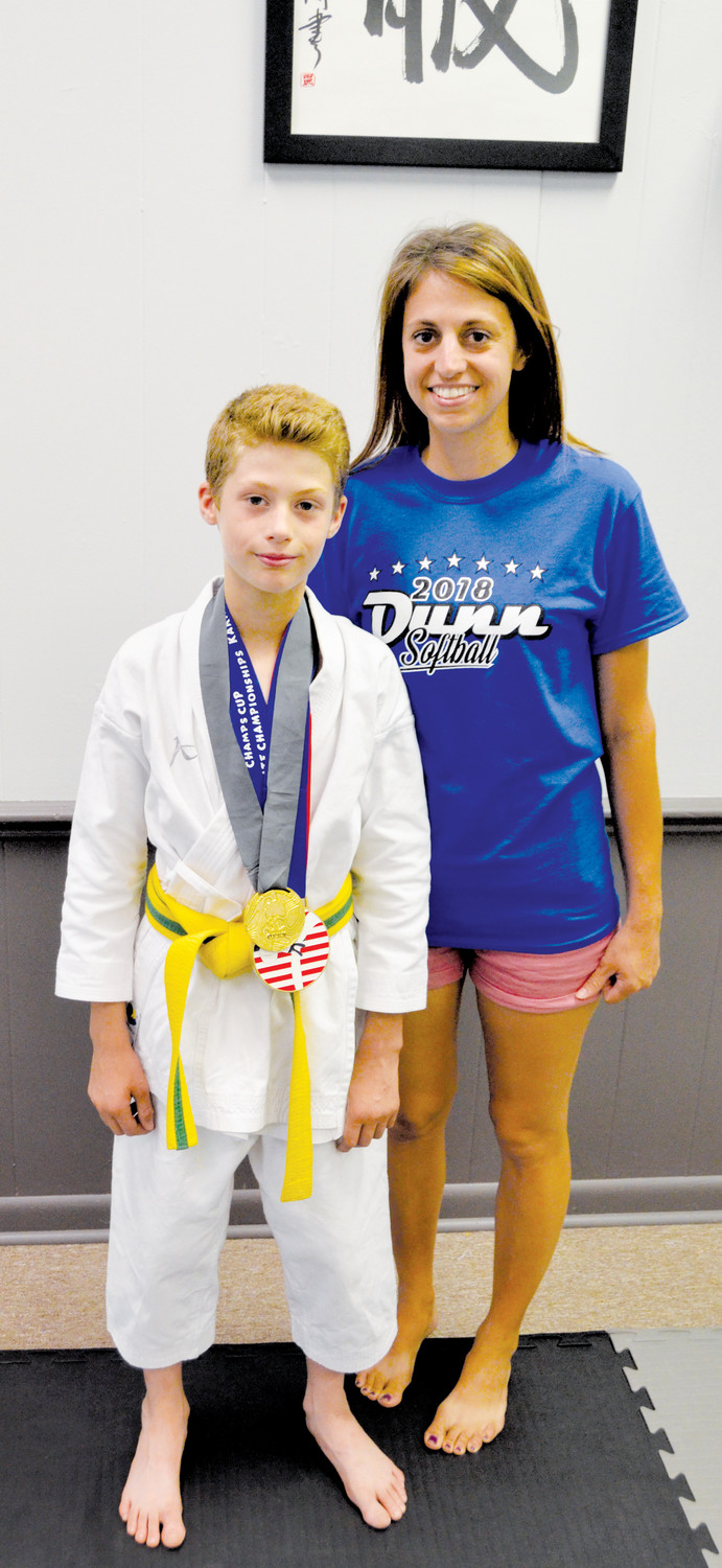 Garen Odum, 9, a student at Wayne Avenue Elementary, stands in the dojo at the Kokufuku School of Martial Arts with his mother, Michelle Odum. Garen has been training at the Dunn location for one year, and was recently awarded a silver medal in Kata and gold medals in Kumate at two out-of-state regional tournaments.